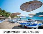 sun loungers on a beach in... | Shutterstock . vector #1034783209
