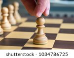 hand moving a white pawn on a... | Shutterstock . vector #1034786725