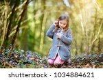 adorable little girl picking... | Shutterstock . vector #1034884621