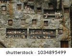 Small photo of Tana Toraja, Indonesia - nov 2009 : rock tombs carved into the rock face and simulacra tau tau exposed on the balconies in Lomo in the Tana Toraja region in Sulawesi
