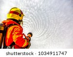 firefighter using extinguisher... | Shutterstock . vector #1034911747