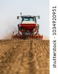 Small photo of Farmer seeding, sowing crops at field. Sowing is the process of planting seeds in the ground as part of the early spring time agricultural activities.