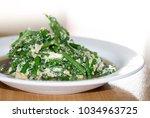 stir in green vegetables in a... | Shutterstock . vector #1034963725