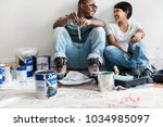 couple painting house wall | Shutterstock . vector #1034985097