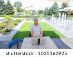 Small photo of Skilled actuary working with laptop and documents at cafe table. Handsome man dressed in white shirt sitting near green plants on sofa and typing with keyboard. Concept of a person compiling and