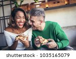 mixed race couple eating pizza... | Shutterstock . vector #1035165079