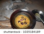 Small photo of Indian spicy Brinjal vegetable making on traditional cookstove called Chulha and in an earthen pot