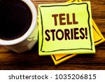Small photo of Handwritten text showing Tell Stories. Business concept for Storytelling Telling Story written on sticky note paper on wooden wood background with coffee cup