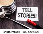 Small photo of Conceptual hand writing text caption showing Tell Stories. Business concept for Storytelling Telling Story written on sticky note paper on wooden wood background. With coffee and marker