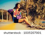 the woman is sitting on the... | Shutterstock . vector #1035207001