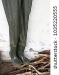 Small photo of Chest wader pants fisherman boots hanging over a pile of woods