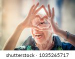Stock photo cute senior old woman making a heart shape with her hands and fingers 1035265717