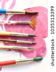 Small photo of Row of artist paintbrushes closeup on artistic canvas
