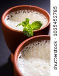 Small photo of Lassie or lassi in terracotta glass - Lassi is an Authentic Indian cold drink made up of curd and milk and sugar, selective focus