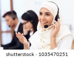 an arab woman works in a call... | Shutterstock . vector #1035470251