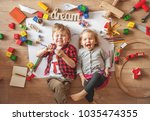 Small photo of Kids drawing on floor on paper. Preschool boy and girl play on floor with educational toys - blocks, train, railroad, plane. Toys for preschool and kindergarten. Children at home or daycare. Top view