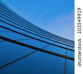 glass facade of an office building in a low angle view - stock photo