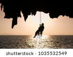 Small photo of Unidentify rope access worker abseil of the cliff at sunrise in Phang Nga bay, southern of Thailand