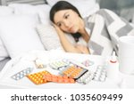 sick woman lying in bed with... | Shutterstock . vector #1035609499