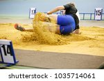 Small photo of Sportsman landing into sandpit in long jump competition. Track and field competitions concept background