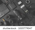 top view of work space photographer with digital camera, flash, cleaning kit, memory card, external harddisk, USB card reader, laptop and camera accessory on black table background - stock photo