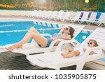 Small photo of Endless summer. Cute baby and mother relaxing at sunbed near pool at resort. A little girl wearing sunglasses. Child and mom sunbathe. Fashion girls, friends, family at resort
