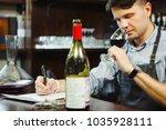 male sommelier tasting red wine ... | Shutterstock . vector #1035928111
