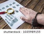 Small photo of the fingerprinting of a criminal in handcuffs, arrest, accused, investigation