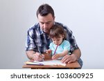 Toddler boy drawing with colored pencils aided by his father - stock photo