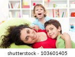 Happy mother and her children playing together at home - motherhood concept - stock photo