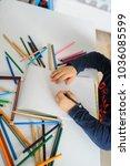 top view of little boy paints... | Shutterstock . vector #1036085599