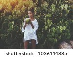 Small photo of Coquettish young cute Brazilian female in front of quickset hedge of cactuses with coconut is quenching her thirst; black flirtatious girl is drinking coco water while standing near wall of cactuses
