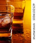 Small photo of Glass of scotch whiskey with natural ice on table in bar.