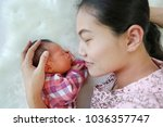 asian mother lying with her son ... | Shutterstock . vector #1036357747
