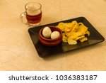 Small photo of Two pickled eggs in ceramic bowl, served with crisps or chips and half pint of English beer.