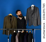 man with beard by clothes rack. ...   Shutterstock . vector #1036391785