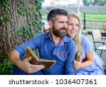 Small photo of Girl with happy face fall in love with bearded man, couple reads poems. Romantic couple holds old books with poems. Date and love concept. Couple in love sit in cafe outdoor, nature background.