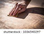 Small photo of Gritty weathered man's hand and sandpaper; hand sanding a table top to refinish with paint or stain