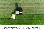 Small photo of Low altitude aerial top down photo of meadow and farmer in tractor cutting the green grass field after this the cut grass can dry and be picked up so it can be used as animal fodder for cows