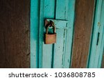 Small photo of The blue wooden door was locked by old metal master key.