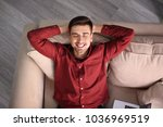 young man resting on sofa at... | Shutterstock . vector #1036969519