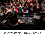 dj with headphone and dj set at ... | Shutterstock . vector #1037012425