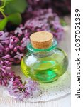Small photo of Essential aroma oil with lilac on wooden background