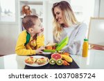 mother making breakfast for her ... | Shutterstock . vector #1037085724