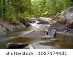 Small photo of Rocky shoreline with coppery color waters from Northern Wisconsin. Scenic view made with time exposure to flatten waves and make moving water appear cotton like. Greenery abound with jagged boulder.