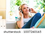 happy young woman listening to... | Shutterstock . vector #1037260165