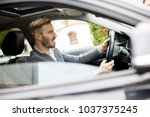 young businessman driving in... | Shutterstock . vector #1037375245