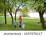 a mother plays the nature with... | Shutterstock . vector #1037470117