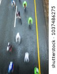 Small photo of Cycling riders road race speed blur motion of cyclists and individual unidentified overhead photo.