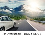 Stock photo white car rushing along a high speed highway toned photo 1037543737